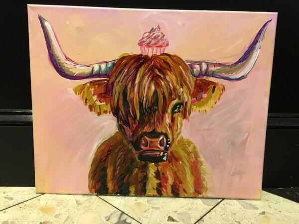 Cow with horns and shaggy hair covering right eye with pink cupcake on her head