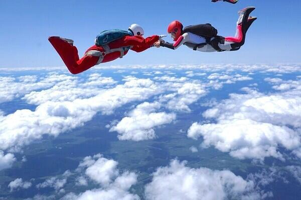 Two parachuters wearing red holding hands with blue skies and clouds below them