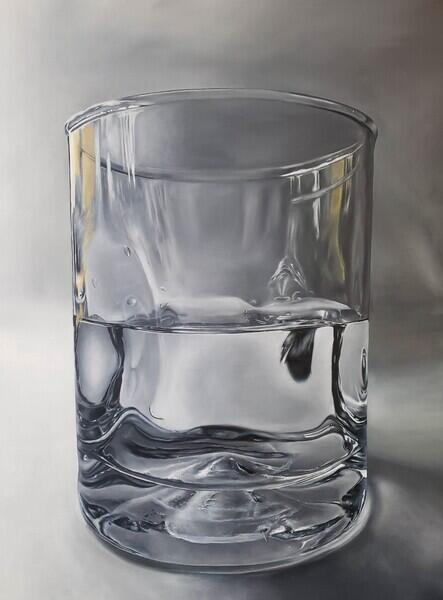 Half filled with water glass on grey background with light painted to look as though it is shining on the glass from only the left
