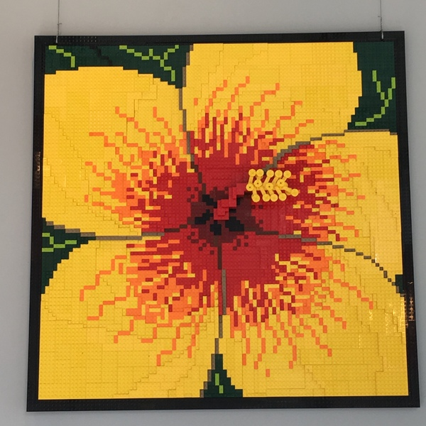 Mural of LEGO pieces hanging on wall Looks like a yellow Hibiscus with red center with black border Completely made of LEGO pieces