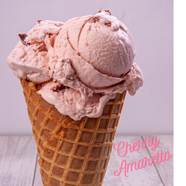 Pink ice cream with pieces of cherries on waffle cone in front of white background Pink text in lower right corner Cherry Amaretto