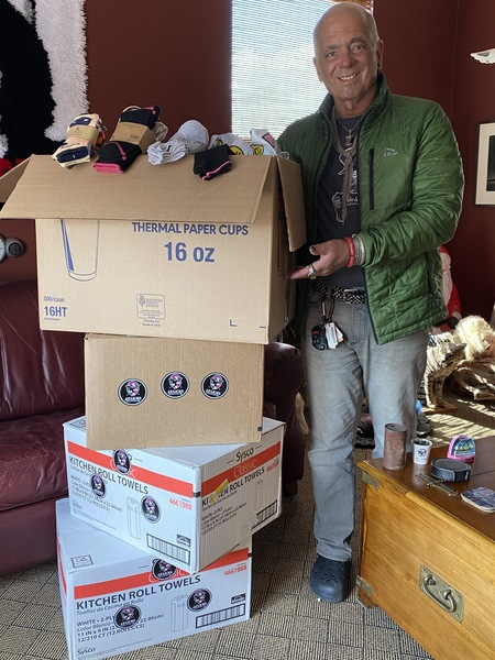 Man in green jacket gesturing toward stack of four cardboard boxes filled with socks