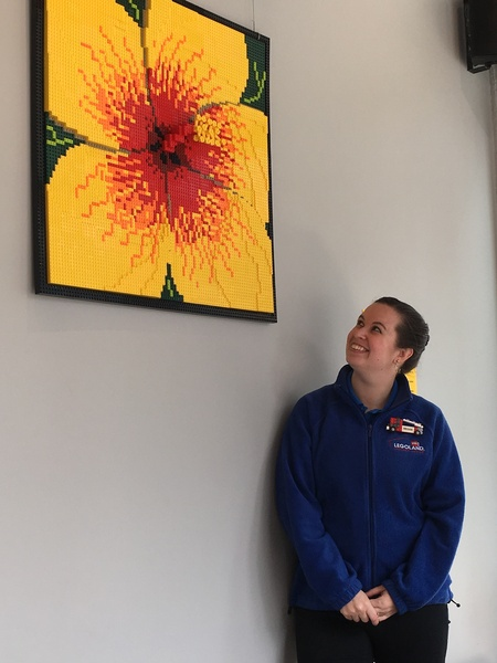 Artist standing under and looking up at a mural made completely of LEGOS Mural looks like a hibiscus with yellow petals and red center surrounded by black border