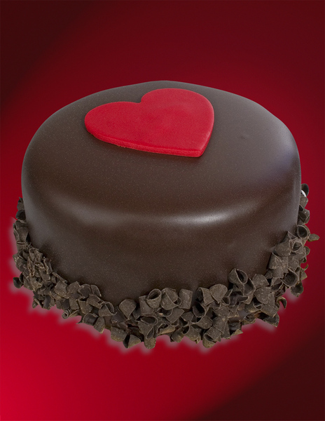Chocolate covered ice cream cake with chocolate shavings along bottom and red fondant heart on top on red background