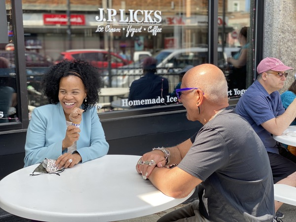 Mayor Janey in blue jacket sitting at white table with chocolate ice cream in a cone smiling and looking off camera with owner Vincent Petryk in black shirt sitting across from her as seen from the left side