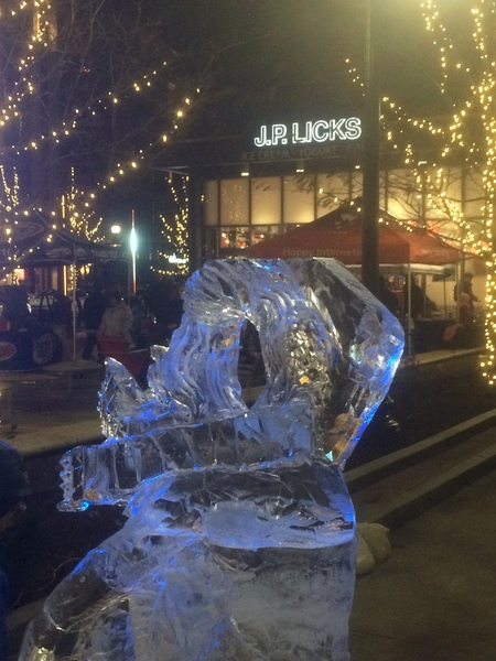 Ice sculpture of hooded figure in front of JP Licks with lights in trees in the middle ground
