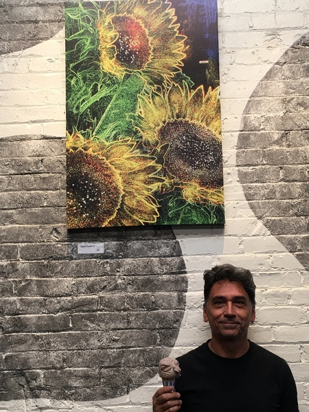 Artist standing in front of art work holding ice cream cone Art work is enlarged neon sunflowers on canvas